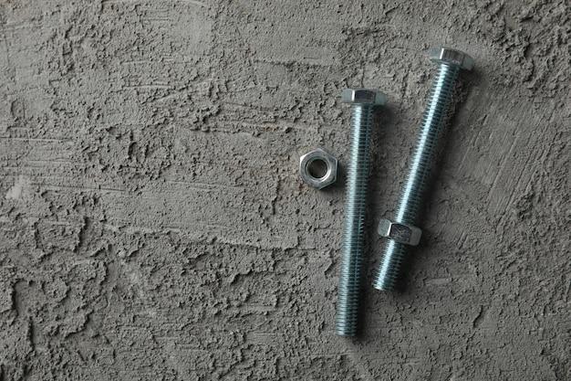 Clous métalliques et écrou sur gris, espace pour le texte