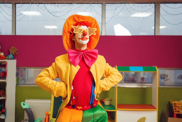 Clown drôle dans des poses de lunettes étoiles dans l'espace pour enfants. fête d'anniversaire célébrant dans la salle de jeux, vacances de bébé dans l'aire de jeux. bonheur d'enfance, loisirs enfantins, divertissement avec animateur