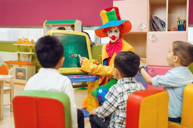 Clown drôle avec des enfants heureux jouent dans l'alphabet à bord.
