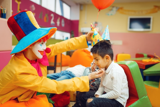 Le clown drôle met une casquette sur la tête du petit garçon.