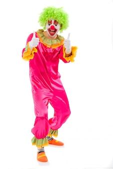 Clown espiègle drôle en perruque verte montrant signe ok.