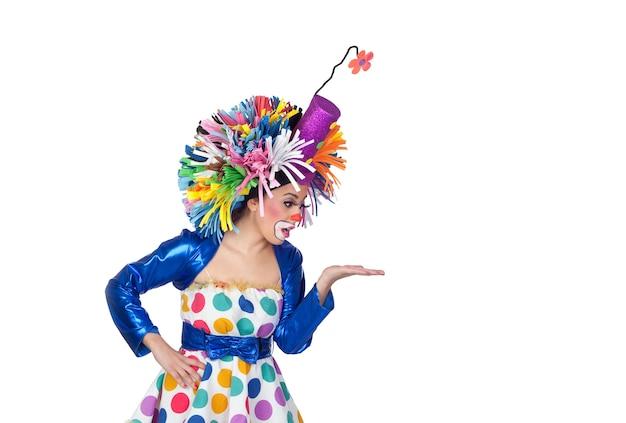 Clown fille drôle cherche quelque chose sur sa main isolé sur fond blanc