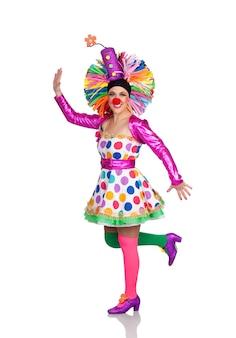 Clown fille drôle avec une grande perruque colorée danse isolé sur fond blanc