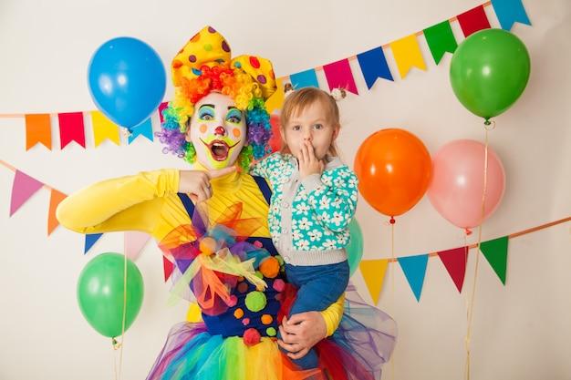 Clown joyeux avec un enfant lors d'une fête colorée