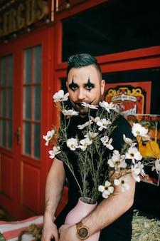 Un clown noir gothique posant avec des fleurs