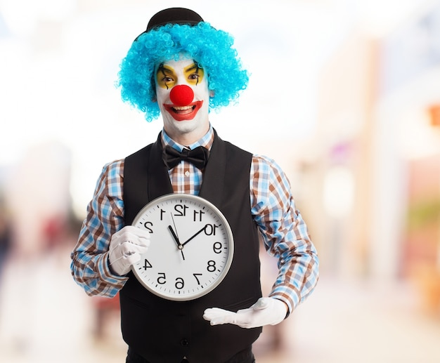 Clown avec perruque bleu montrant une horloge