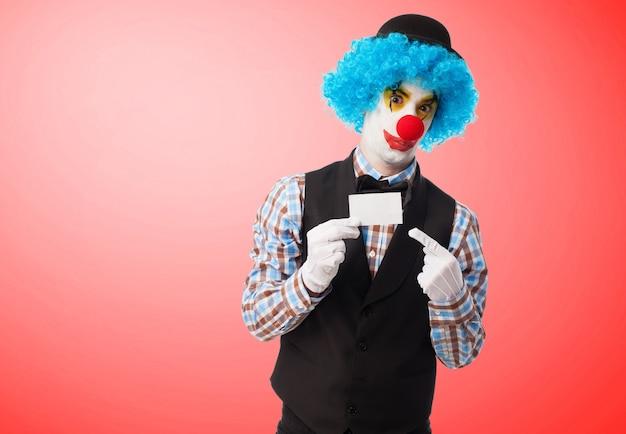 Clown tenant et pointant une carte blanche