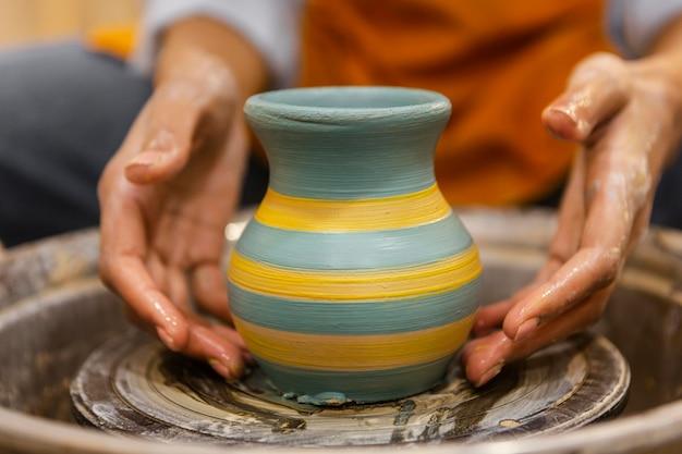 Clsoe les mains faisant de la poterie