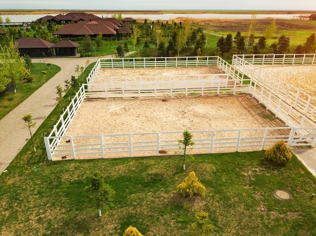 Club equestre de pays. vue d'en-haut. terrain pour marcher, faire de l'exercice et travailler les chevaux à l'extérieur.
