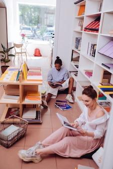 Club de lecture. homme à la peau foncée attentif s'appuyant sur le mur tout en lisant un livre