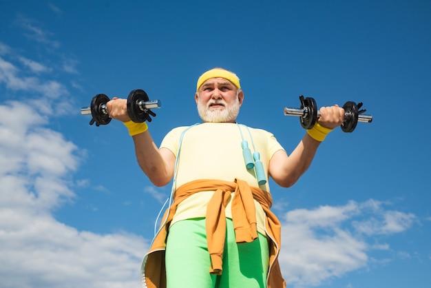 Club de remise en forme ou centre de réadaptation pour personnes âgées retraitées senior sport homme soulevant des haltères i...