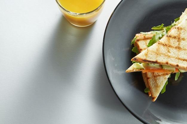 Club sandwich au saumon et légumes sur assiette et jus d'orange frais
