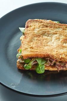 Club sandwich avec concombre, salade, jambon et œufs sur la plaque noire