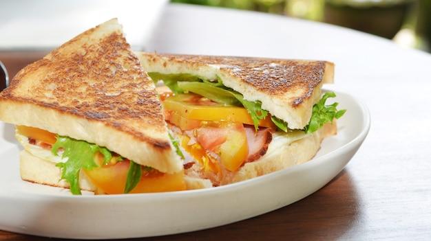 Club sandwich avec du café sur fond de bois