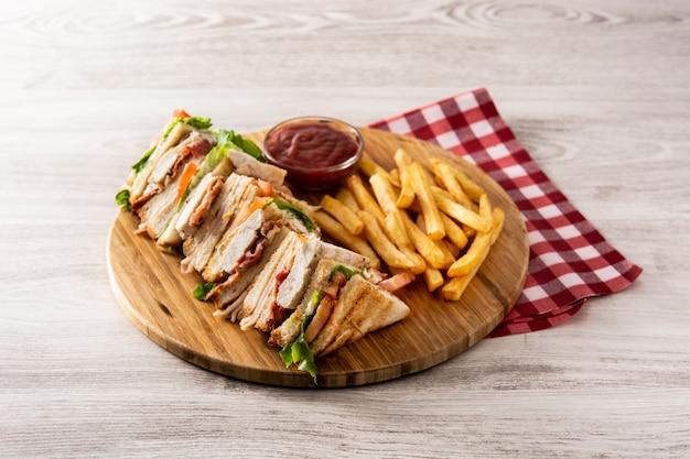 Club sandwich et frites sur table en bois