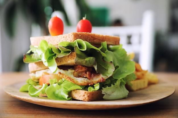 Club sandwich avec jambon, bacon, tomate, fromage, œufs et frit sur fond de bois