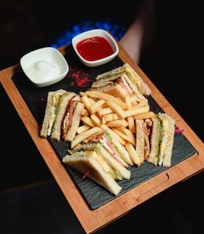 Club sandwich servi avec des frites