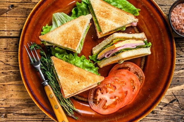 Club sandwiches grillés avec jambon de porc, fromage, tomates et laitue sur une assiette