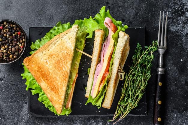 Club sandwiches avec jambon de porc, fromage, tomates et laitue sur une planche à découper en bois