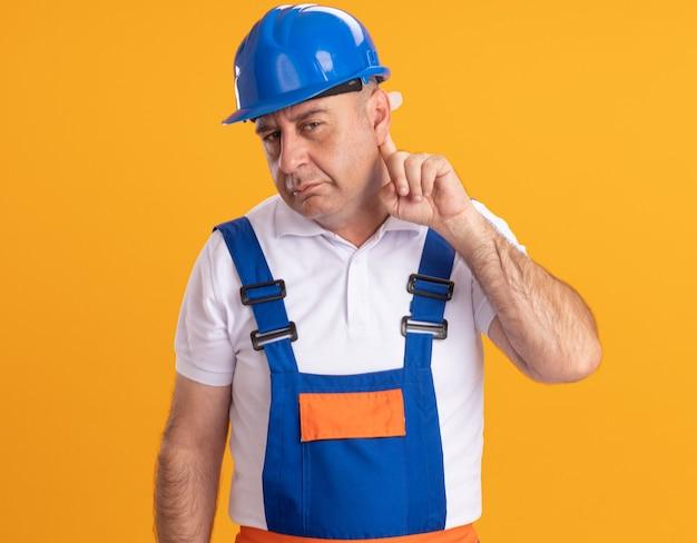 Clueless caucasian adulte constructeur homme en uniforme tient le doigt derrière l'oreille sur orange