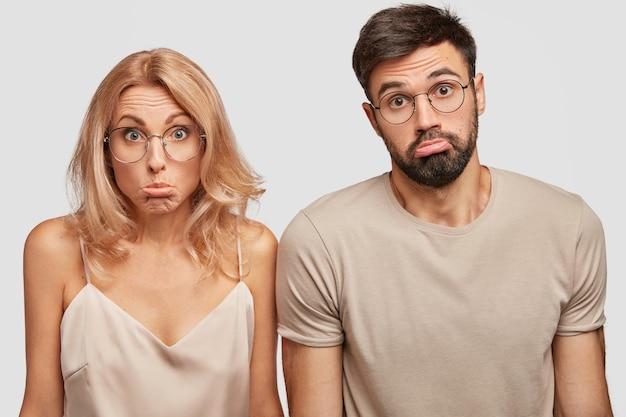 Clueless douteux couple de famille haussent les épaules dans la confusion, les lèvres de la bourse, ne sais pas où passer des vacances
