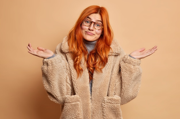 Clueless douteux rousse jeune femme de race blanche écarte les paumes et fait face à un choix difficile porte des gestes de manteau de fourrure marron indécis.