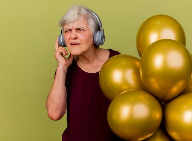 Clueless femme âgée sur le casque se dresse avec des ballons d'hélium à côté isolé sur mur vert olive avec copie espace