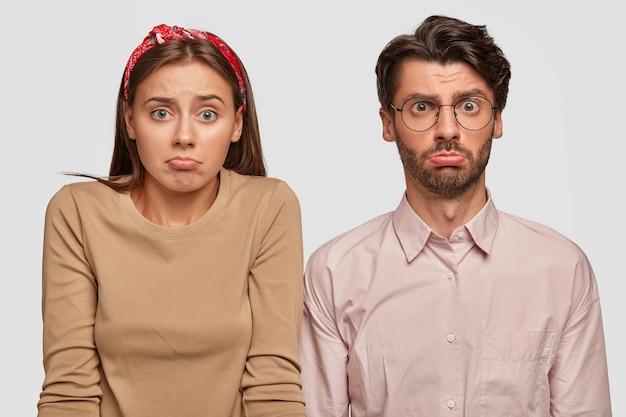 Clueless jeune couple posant contre le mur blanc