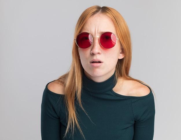 Clueless jeune fille rousse au gingembre avec des taches de rousseur dans des lunettes de soleil regardant la caméra sur blanc