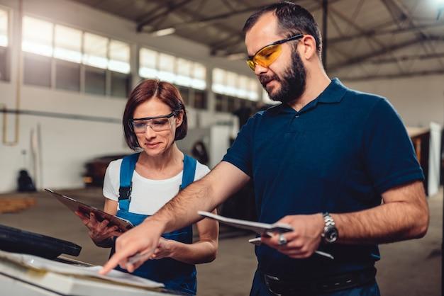 Cnc opérateur et ingénieur industriel vérifiant le dessin du produit