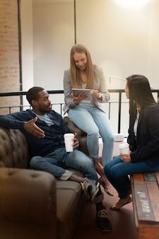 Co travailleurs parlant assis sur un canapé avec tablette