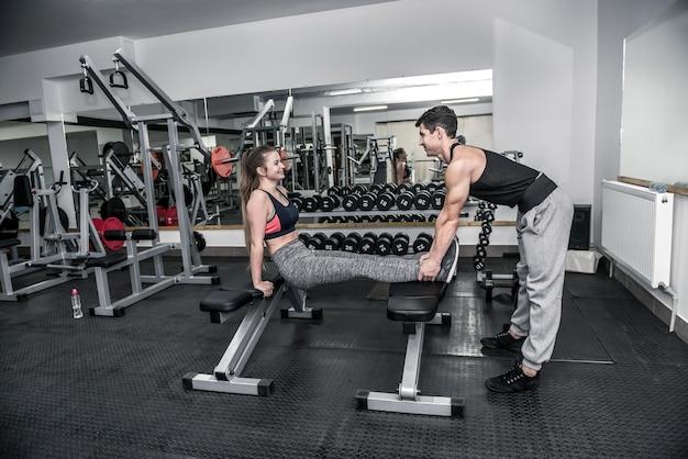 Coach personnel aidant à la jeune femme dans la salle de sport