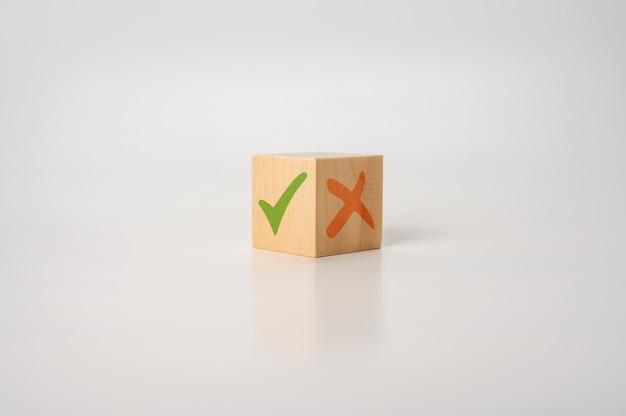 Coche et croix x sur le concept des avantages et des inconvénients des cubes en bois