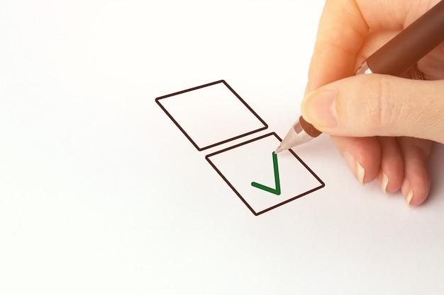 Coche de dessin à la main masculine dans la case à cocher. image recadrée de la main qui écrit sur la liste de contrôle.