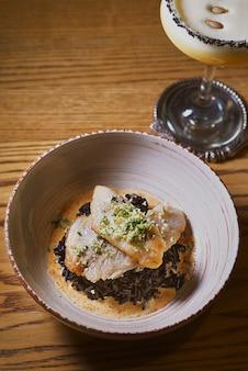 Cocktail d'alcool de citrouille dans un verre et du riz noir et du poisson dans une assiette sur la table