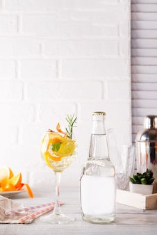 Cocktail d'alcool avec des fruits frais et des baies avec une bouteille de tonique