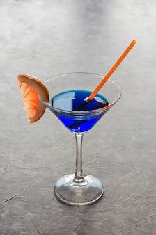 Cocktail alcool à la liqueur bleue sur une table grise, avec une tranche de pamplemousse.