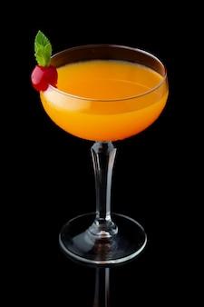 Cocktail d'alcool orange à la menthe et cerise isolée sur fond noir