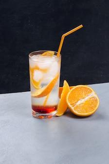Cocktail d'alcool orange avec tranche de fruits orange sur fond gris et noir