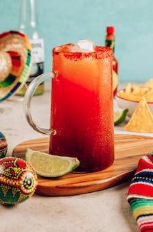 Cocktail alcoolisé bloody mary d'inspiration mexicaine michelada avec bière jus de citron vert jus de tomate sauce épicée et épices