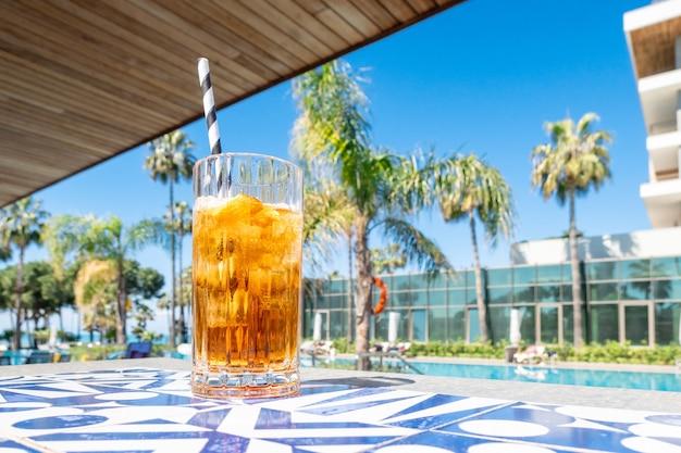 Cocktail alcoolisé frais avec de la glace en verre sur la piscine
