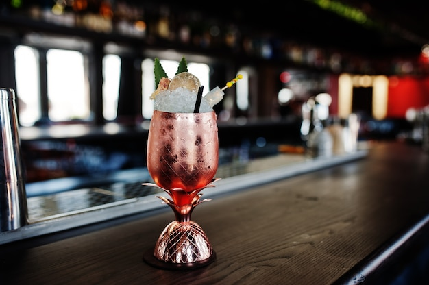 Cocktail alcoolisé avec glace en verre bronze sur table de bar