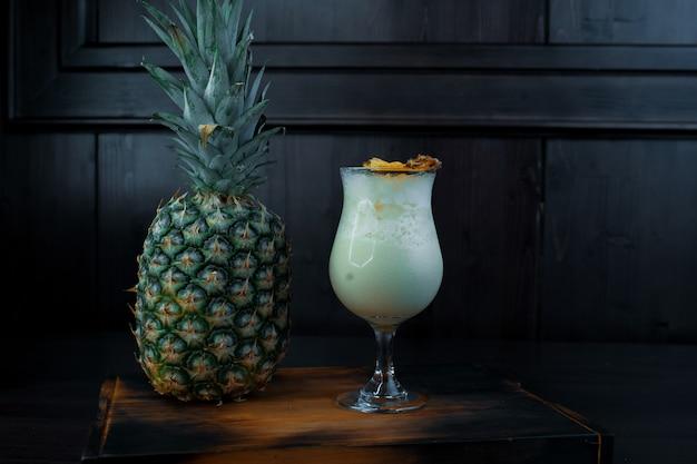 Cocktail alcoolisé laiteux blanc doux avec du jus de glaçons et tonique avec de la vodka sur une table brune près d'un ananas frais dans un bar. boissons alcoolisées. vie de boîte de nuit