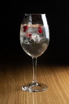 Cocktail alcoolisé spritz aux canneberges et glace dans un grand verre à vin transparent sur une table en bois