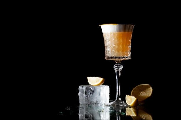 Cocktail d'ambre classique aux agrumes et à la glace sur fond noir