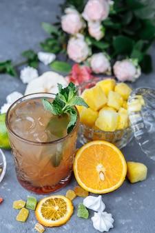 Cocktail d'ananas rafraîchissant froid au citron vert et à la menthe pour une chaude journée d'été sur une surface grise décorée de fruits confits à la menthe et aux cubes d'ananas idée de mojito limonade maison avec des glaçons