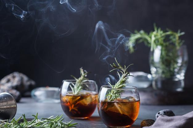 Cocktail à l'ancienne au romarin fumé sur une table