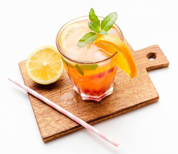 Cocktail à angle élevé avec orange sur une planche à découper et copie-espace
