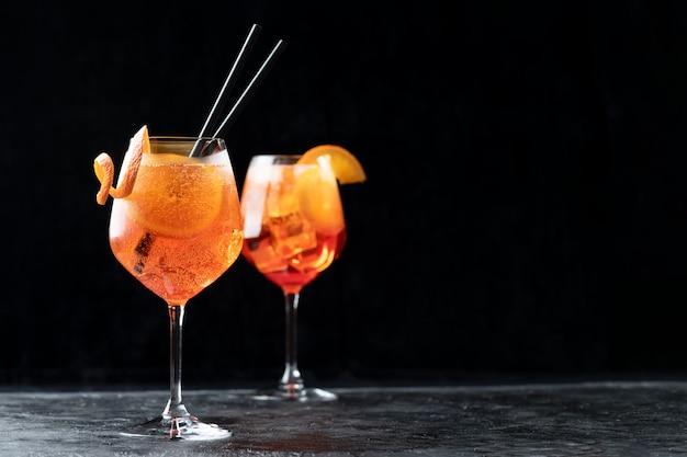 Cocktail aperol spritz italien classique en verre sur fond noir, close up