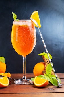 Cocktail aperol spritz et outils de bar. cocktail italien aperol spritz et une orange tranchée sur fond sombre. aperol spritz cocktail à la menthe fraîche